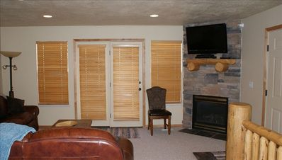 Living Area with french Door to Balcony, Gas Fireplace and New Flat Panel TV