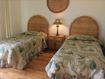 The guest bedroom features two twin beds, a six drawer dresser and full closet.