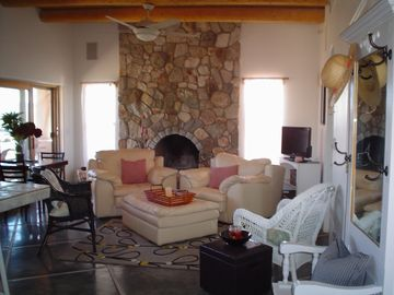 living room with large stone fireplace (wood burning)