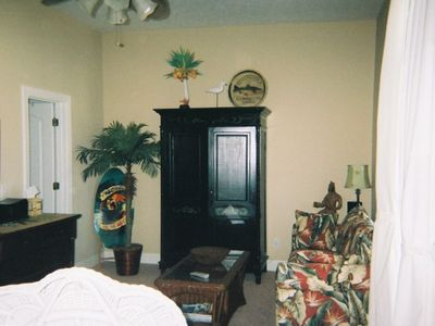 Master bedroom on second floor has king bed,sofa,armoire with tv,bath,patio