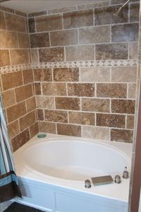 Master Bathroom travertine walls in bathtub/shower