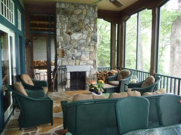 Screened porch with fireplace, seating, and dining table