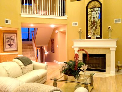 Great room with fireplace looking towards entrance.
