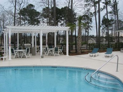 Large pool with picnic area, grill, lounge chairs, and bathrooms