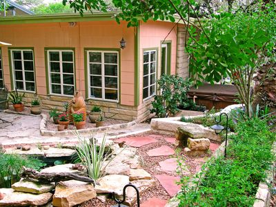 Back yard is a peaceful retreat with covered seating next to a fish pond.