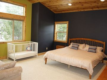 The spacious master bedroom has king-sized bed and optional crib