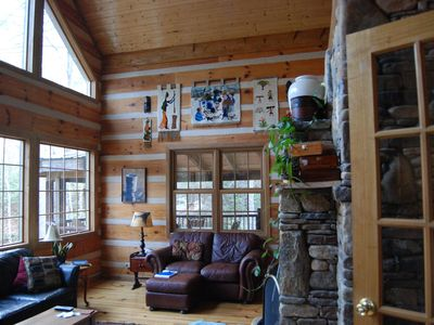 Two story sun room with large stacked rock fireplace, pine planked floors!
