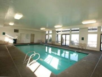Indoor Heated Pool overlooking the lake with attached patio, tables and grill.