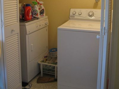 Full-sized washer and dryer in enclosed laundry closet.