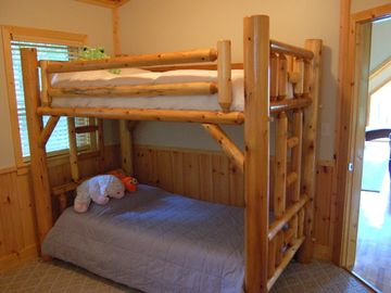 The third bedroom has a desk, a twin bunkbed, and a sweet playtime cubby!
