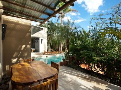 Backyard area with private pool, lounge chairs and dining table