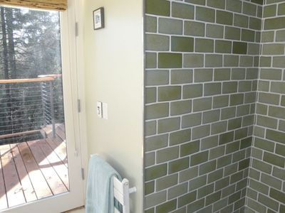 recycled wine bottle shower, towel heater and door to deck