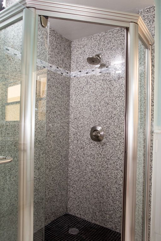 Large granite walk-in shower in the hallway bathroom.