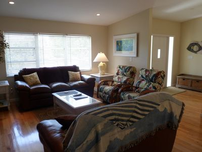 .View of Living Room and Entry with comfy high end seating and bright decor!