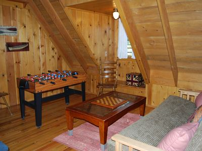 Upstairs loft with game table, futon bed, coffee table and adjacent laundry area