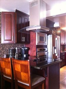 Deeper view of Kitchen's peninsula and Keurig coffee maker,glass tile backsplash