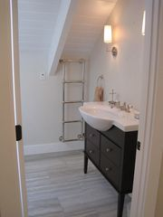Surfside Nantucket property rental photo - Chic bathroom w/heated floors/towel rack - shower has skylight.