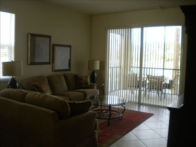 Living room with flat screen tv & step-out lanai overlooking golf course & water