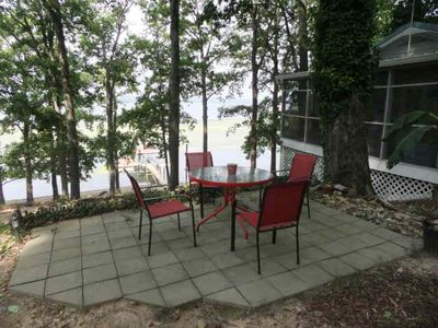 Patio next to the cottage. There is a firepit and charcoal grill by the patio.