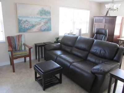 New upscale Leather couch and a desk behind to watch TV or view internet