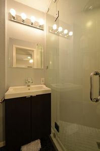Modern full shower with frameless glass wall.