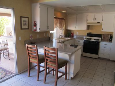 Kitchen with gas stove, granite counter-tops, eating bar for two