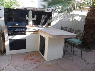 Outdoor kitchen with custom tile, night lighting, sink, gas grill. - Phoenix house vacation rental photo