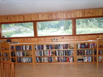 Books under the bar that overlooks the river and valley.