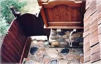 Overhead view. Stone & cedar, private outdoor hot shower with tropical rainhead.