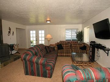 The family room has 3 couches, a large screen TV, foosball table, & wood stove