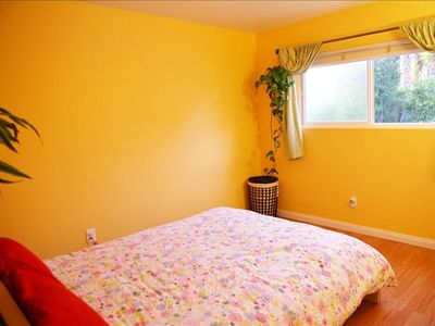 Yellow Bedroom with Queen Bed Overlooks Tropical Yard and Pool