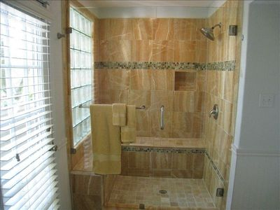 Enjoy this huge honey onyx walk-in shower with view looking at downtown skyline