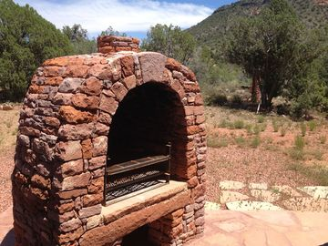 Outdoor stone kiva fireplace with mountain views.