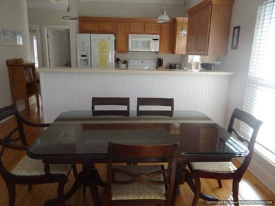 Dine with family and friends at the large dining room table and kitchen area.