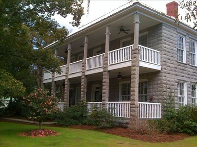 Built in 1907 of granitoid block, with two large porches and tall windows.