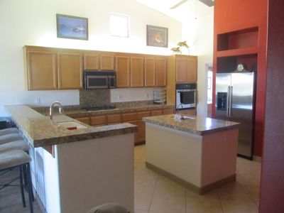 Kitchen with breakfast bar, wet island, stainless appliances and built-in desk