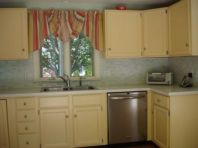 Bright yellow cabinets with sea glass mosaic tile