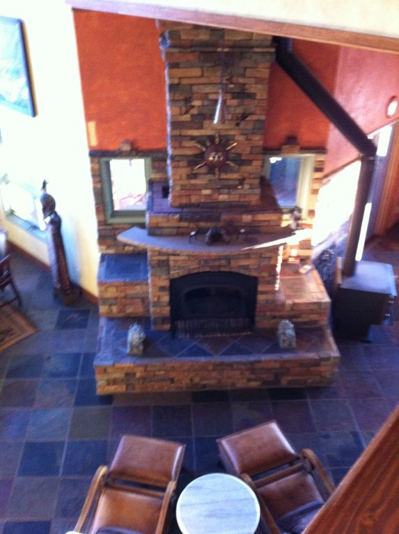 View from loft of 1 seating area in front of stacked rock wood burning fireplace