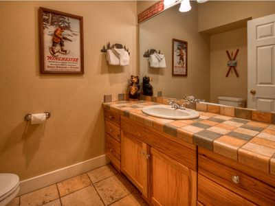 Half bath with tile counter and floors on main floor, true Montana feel.