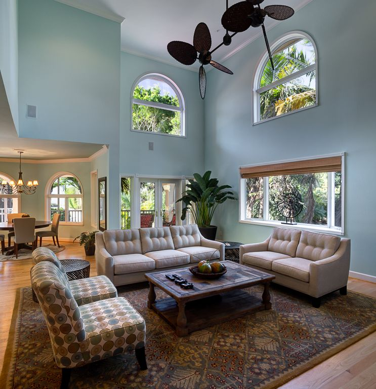 A grand, open great room with beautiful light and tropical designer furnishings.