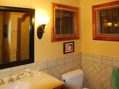 The en-suite master bath has an arched shower, Italian tile, and teak accents.