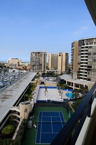 View from balcony overlooking pool and tennis court