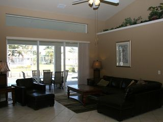 Vacation Homes in Marco Island house photo - Comfortable living room overlooking pool and lagoon.