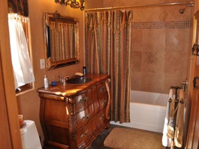 Full bath off of Office/bedroom three. Note hammered copper sink & custom vanity