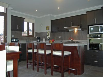 Counter height breakfast bar. Granite counter top expands work area. Open shelves underneath. Lots o