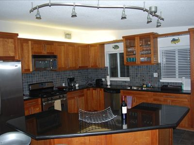 Fully stocked gourmet kitchen with 6 barstools on the island