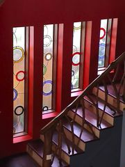 Sanur house photo - Stained glass vertical windows behind ironwood stairs & coffee-branch banister.