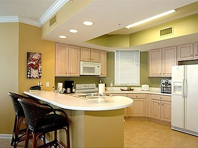Kitchen with breakfast bar, window over sink with view of tennis courts & Destin