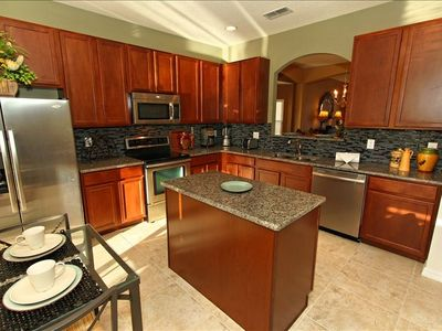 Luxury kitchen - stainless appliances, designer backsplash, granite counters.