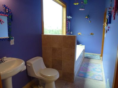 Kids bathroom with full bath, Mountain views adjacent laundry room.